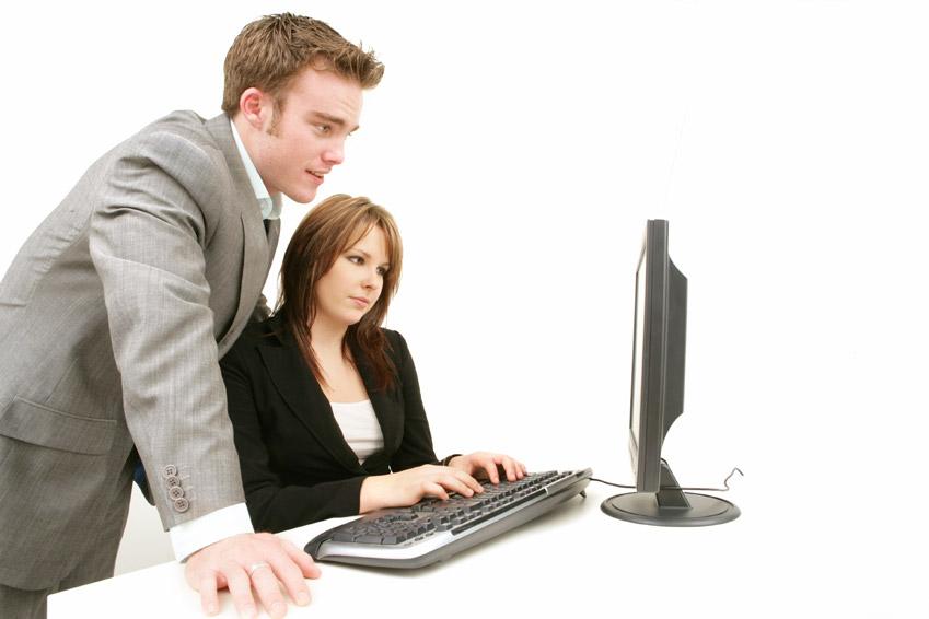 Pareja de trabajadores mirando el monitor del ordenador
